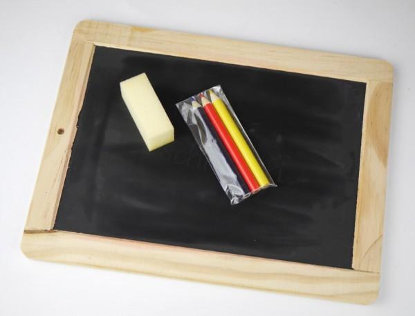 Schultafel mit Buntstiften und Schwamm